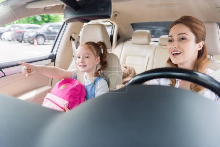portrait of smiling mother driving car with daughter pointing away near by