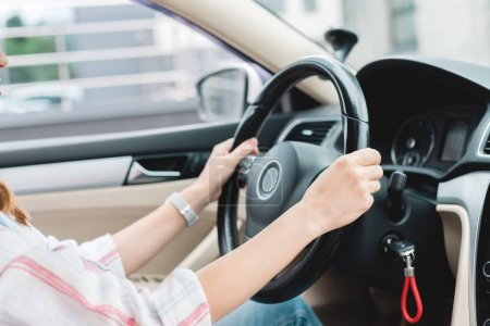 partial view of woman with hands on steering wheel driving car