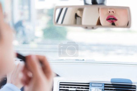 partial view of businesswoman applying lipstick while driving car
