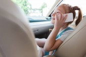 side view of smiling kid talking on smartphone in car
