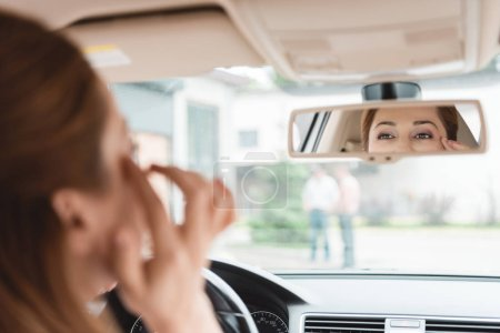 partial view of woman looking at mirror while driving car