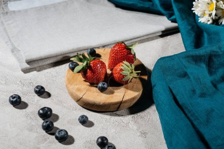 Raw strawberries and blueberries on wooden board