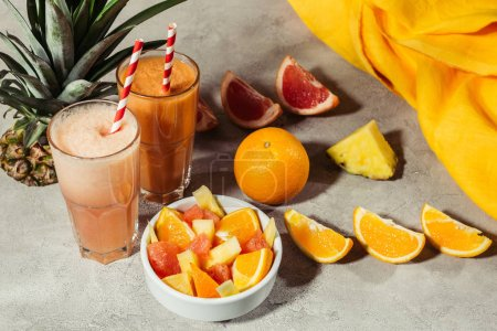 Glasses with tropical fruits juice and citrus pieces on grey table