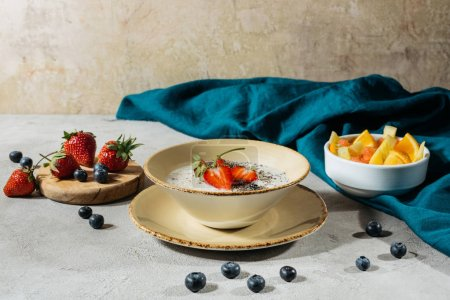 Healthy breakfast with chia seeds bowl and ripe fruits on table with tablecloth