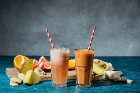Photo pour Verres avec jus et morceaux de fruits mûrs sur table bleue - image libre de droit
