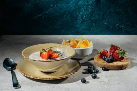 Healthy breakfast with chia seeds bowl and berries on greytable