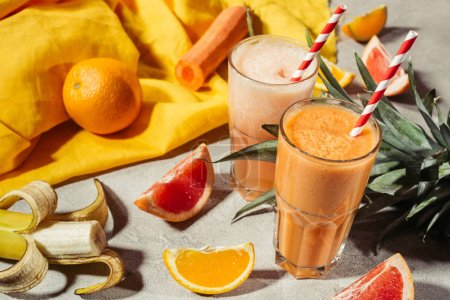 Glasses with tropical fruits juice and fruit pieces on grey table