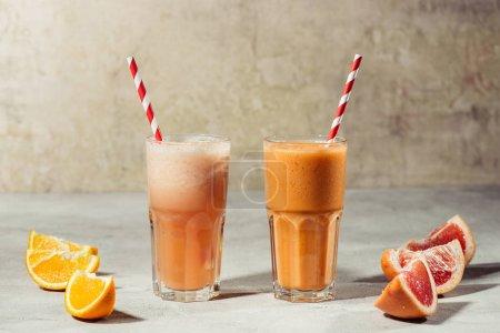 Photo pour Jus frais dans des verres avec morceaux d'orange et de pamplemousse sur la table - image libre de droit