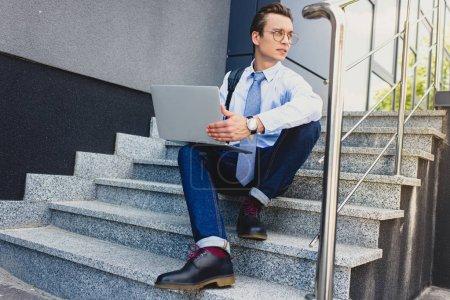 Photo pour Beau jeune freelance avec ordinateur portable assis dans les escaliers et la recherche. - image libre de droit