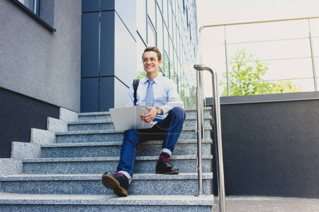 handsome smiling young freelancer in eyeglasses sitting on stairs and using laptop