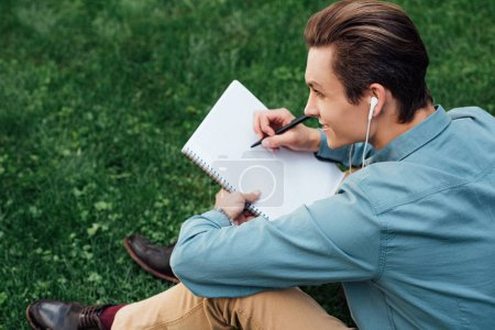 high angle view of smiling young man in earphones taking notes in blank notebook and looking away while sitting on grass