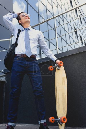 smiling young businessman in eyeglasses standing with longboard and looking away