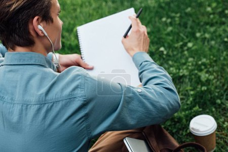 cropped shot of man in earphones writing in blank notebook while sitting on grass