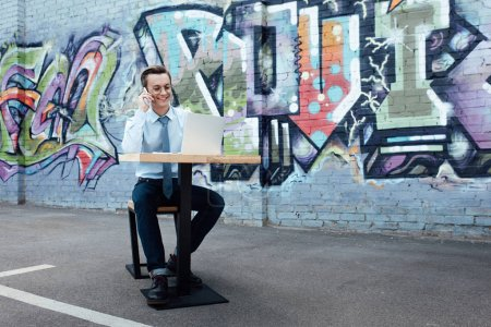 Photo pour Souriante jeune freelance en lunettes de vue parler de smartphone et à l'aide d'ordinateur portable tout en étant assis sur la rue - image libre de droit