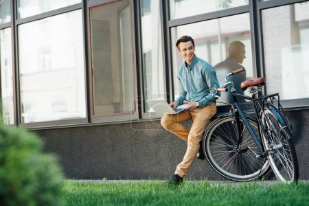 smiling young man using laptop and looking away while leaning at modern building