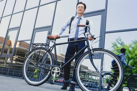 low angle view of handsome young businessman in eyeglasses standing with bicycle near modern building