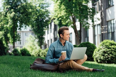 smiling young freelancer with coffee to go sitting on grass and using laptop