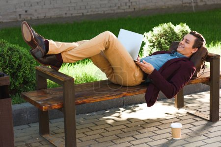 handsome smiling young freelancer lying on bench and using laptop