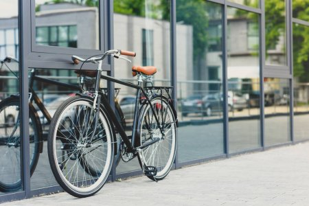 Photo for Comfortable bicycle reflected in modern building on empty street - Royalty Free Image