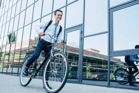 Photo pour Beau jeune homme souriant en lunettes et vêtements formels vélo d'équitation sur la rue - image libre de droit