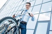 low angle view of handsome young man in eyeglasses standing with bicycle and looking at camera