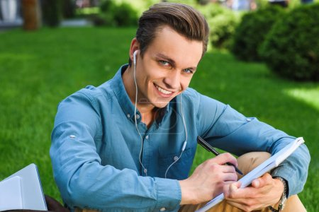 handsome young man in earphones taking notes and smiling at camera