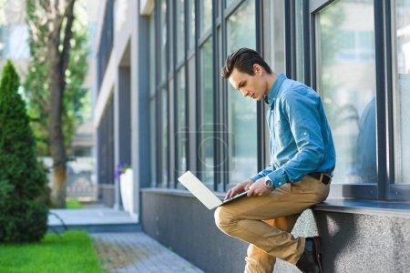 side view of young freelancer using laptop outside modern building