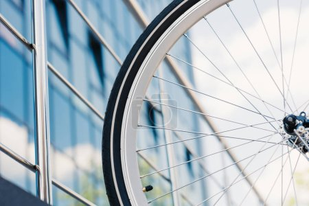 close-up view of bicycle wheel with tyre outside modern building, selective focus