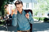 handsome young man talking by smartphone and smiling at camera on street
