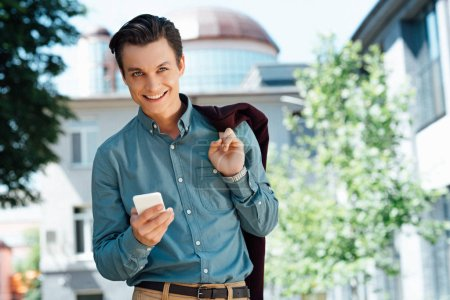 handsome young man holding smartphone and smiling at camera
