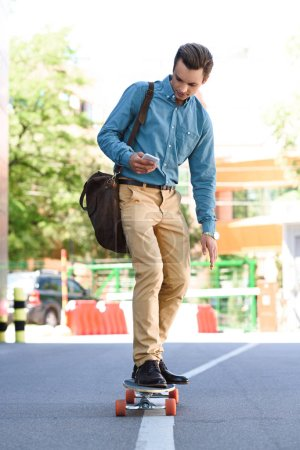 handsome young man using smartphone and riding longboard on street