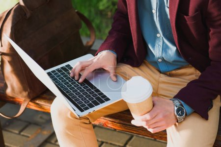 cropped shot of young freelancer holding paper cup and using laptop while sitting on bench
