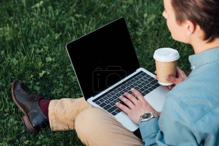Photo pour Recadrée tir de pigiste, boire du café et à l'aide de portable sur l'herbe - image libre de droit