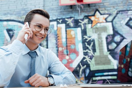 handsome smiling young freelancer in eyeglasses talking by smartphone and using laptop
