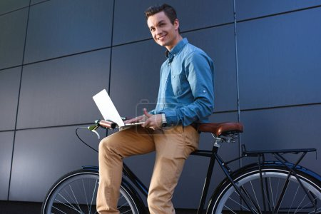 Photo for Smiling young male freelancer sitting on bike and using laptop - Royalty Free Image