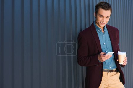 Photo for Handsome young man with coffee to go using smartphone and smiling at camera - Royalty Free Image