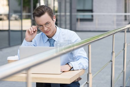 Photo for Young freelancer in eyeglasses using laptop while sitting outside modern building - Royalty Free Image