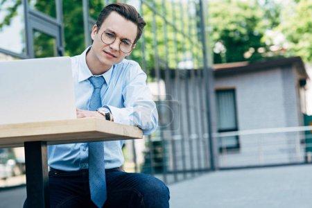 Photo pour Beau jeune homme d'affaires à lunettes à l'aide d'ordinateur portable tout en restant assis à l'extérieur - image libre de droit