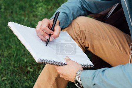 Photo pour Plan recadré de jeune homme écrivant dans un carnet vierge assis sur l'herbe - image libre de droit