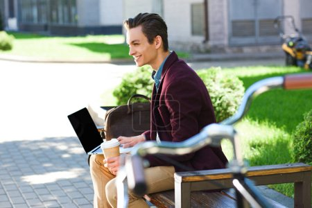 side view of smiling young man using laptop with blank screen on bench
