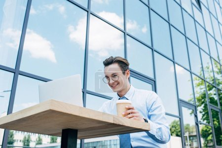 Photo for Low angle view of smiling young freelancer holding paper cup and using laptop outside modern building - Royalty Free Image