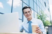 low angle view of smiling young businessman using laptop and holding paper cup