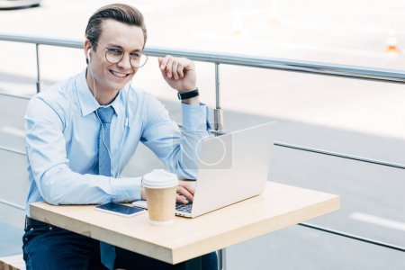 smiling young businessman in eyeglasses using laptop and earphones outside