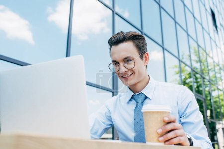 handsome smiling young businessman in eyeglasses using laptop and holding paper cup outside modern building