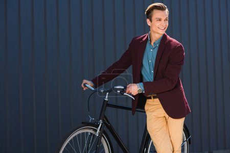 Photo for Handsome smiling young man standing with bicycle and looking away - Royalty Free Image