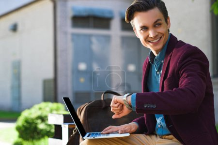handsome smiling young man using laptop and checking wristwatch