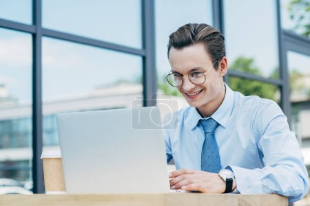 handsome smiling young man in eyeglasses using laptop outside modern building