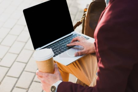 Photo for Cropped shot of man holding paper cup and using laptop with blank screen on street - Royalty Free Image