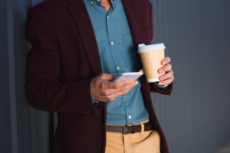 cropped shot of young man holding paper cup and using smartphone