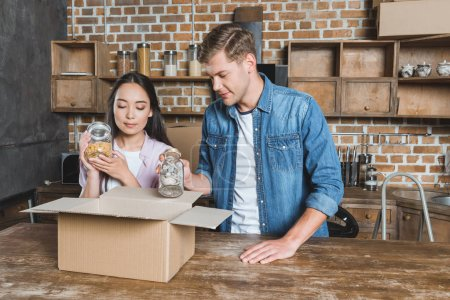 Photo for Young interracial couple unpacking boxes while moving into new home - Royalty Free Image